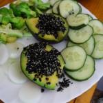 Avocado mit gekeimtem schwarzem Sesam, Gurken, Borkkoliröschen und Zwiebelringen