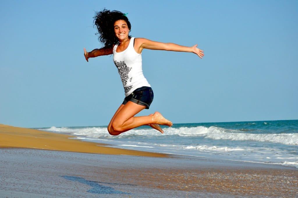 Frau springt in die Luft am Strand