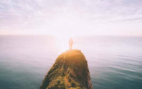 Mann auf Fels am Meer