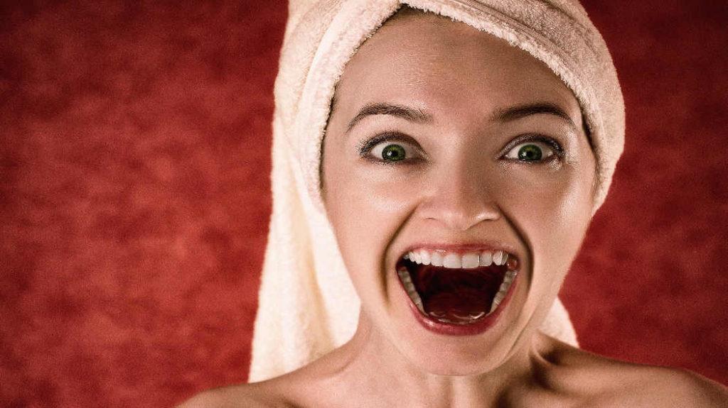 Kann man Karies heilen bzw. stoppen? Bild einer Frau mit offenem Mund und weißen Zähnen